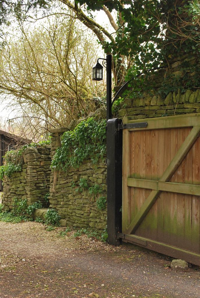 каменный забор в саду калитка